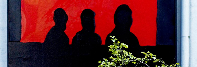 Eine Hauswand. Im Vordergrund einige Zweige. Auf die Wand wurde ein Bild gemalt: Drei Oberkörper, schwarz auf rotem Grund. Wie Zuschauer in einem Kino.