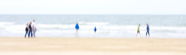 Ein verschwommener Strand im Winter. Drei Menschenpaare verteilen sich darauf wie Farbkleckse.